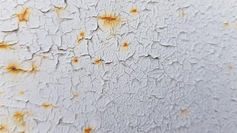 Il bianco ha dipinto la struttura incrinata con le crepe arrugginite rosse fotografie stock