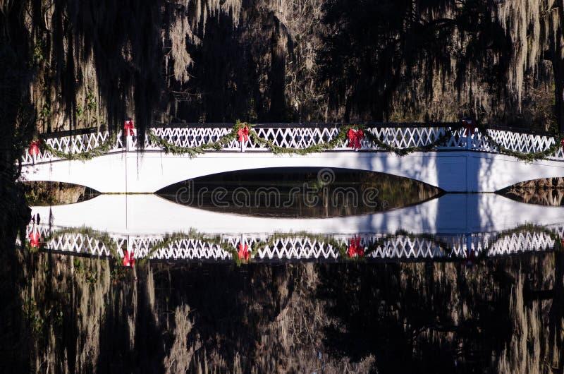 Il bianco ha incurvato il ponte pedonale sopra uno stagno della riflessione, decorato per il Natale alla piantagione Charleston d fotografie stock