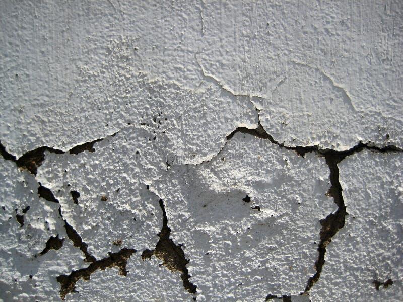 Il bianco incrinato ha colorato la parete esposta a struttura delle forme dell'aria aperta immagine stock