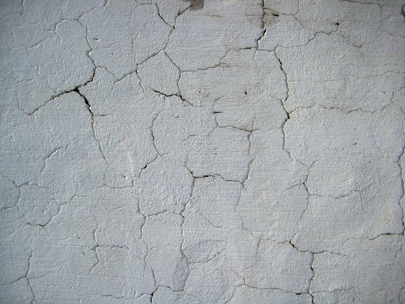 Il bianco incrinato ha colorato la parete esposta a struttura delle forme dell'aria aperta fotografia stock libera da diritti