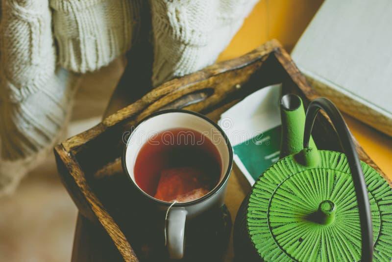 Il bianco sporco ha tricottato il maglione che appende sopra la sedia di legno, tazza con il tè rosso della frutta, vaso in vasso immagini stock