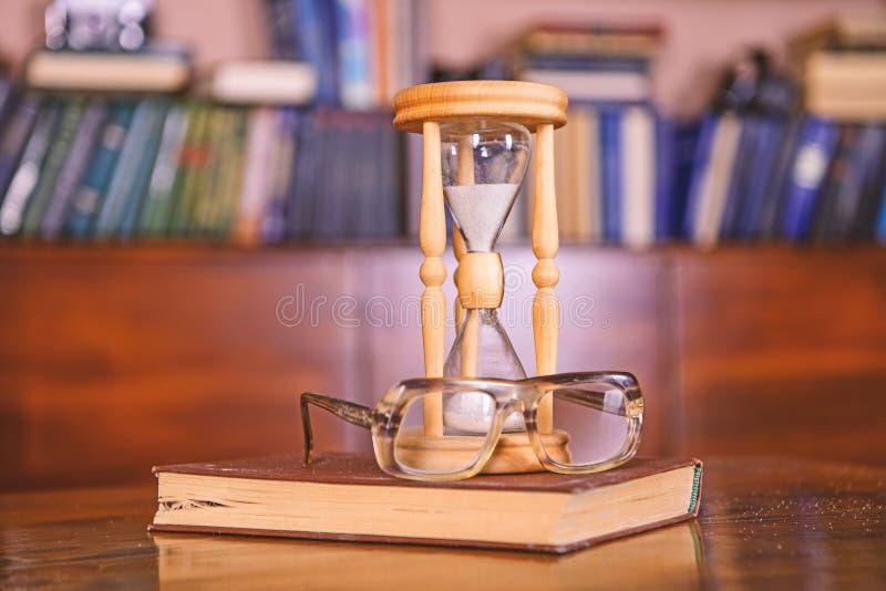 Il bibliotecario attribuisce il concetto Clessidra che conta tempo vicino agli occhiali antiquati Sabbia che cade dentro di fotografie stock