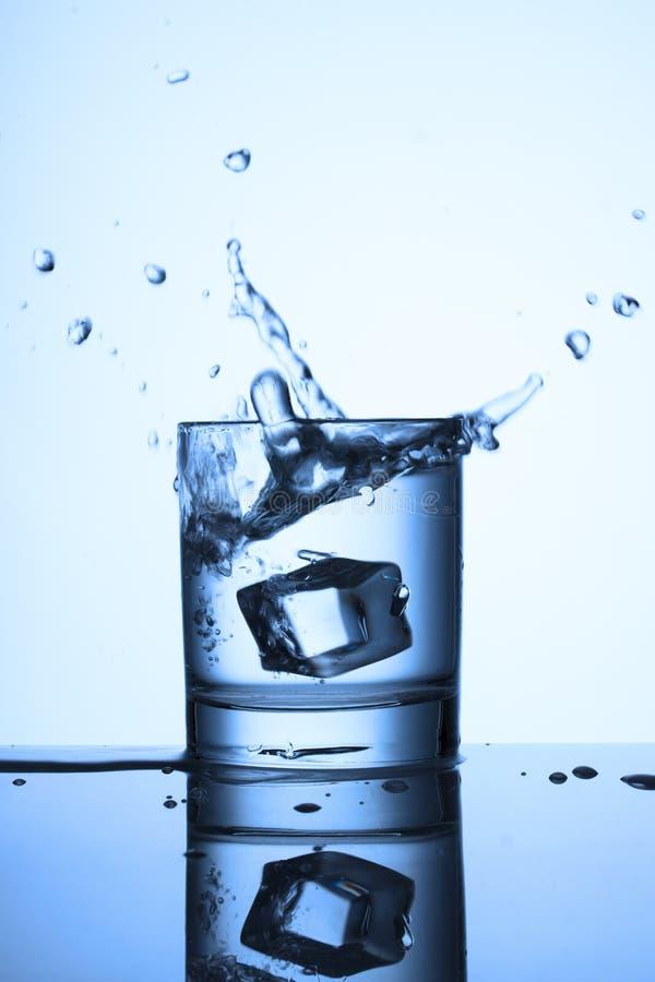 Il bicchiere d'acqua con un pezzo di ghiaccio che cade sul fondo e bello spruzza immagini stock libere da diritti