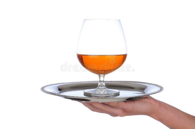 Il bicchiere da brandy di brandy sul cassetto ha tenuto dalla mano dei wonams fotografia stock