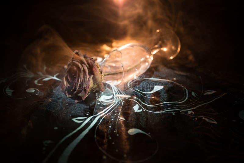 Il bicchiere di vino rotto ed appassito è aumentato su fondo scuro Una rosa appassente significa l'amore perso, divorzio, o una c immagini stock