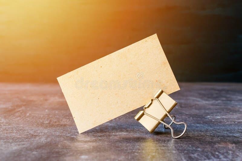 Il biglietto da visita dal mestiere ha riciclato la carta con la clip del raccoglitore del metallo sulla tavola immagine stock libera da diritti