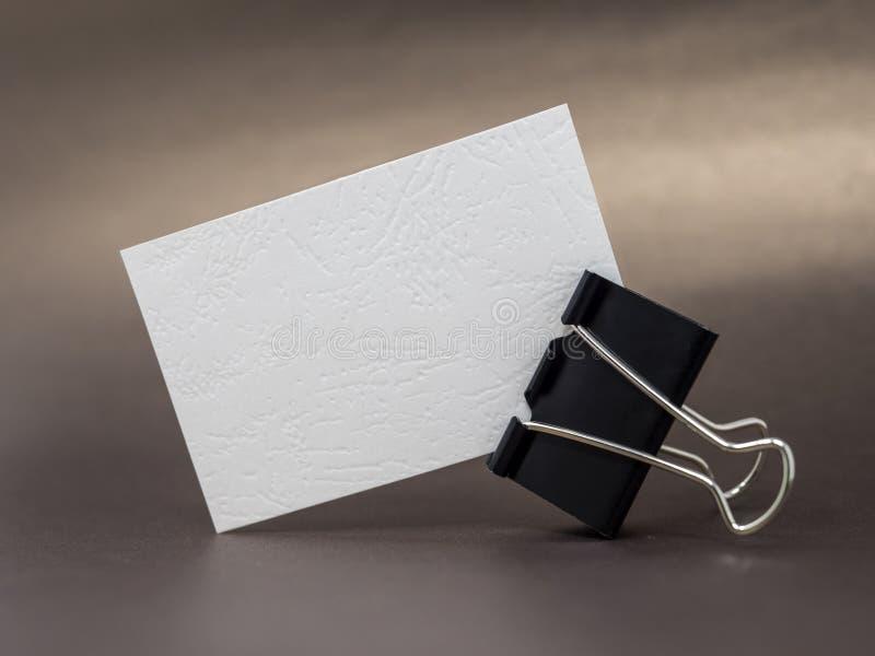 Il biglietto da visita strutturato in bianco ha tenuto dalla clip del raccoglitore su una superficie marrone fotografia stock