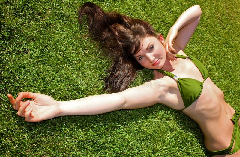il bikini giù erba il modello di menzogne fotografie stock libere da diritti