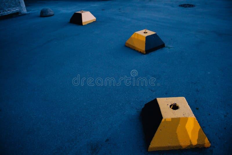 Il blocco in calcestruzzo della piramide gialla tronca contro lo sfondo di asfalto blu immagine stock