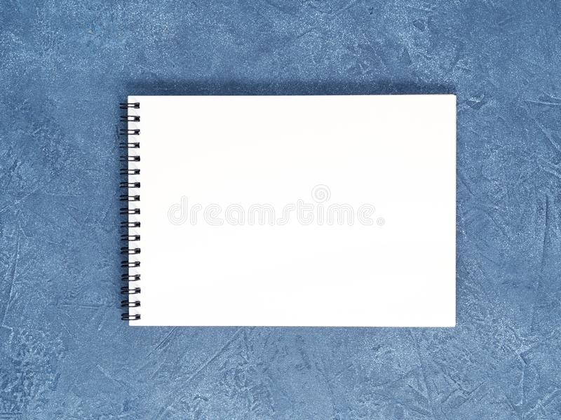 Il blocco note aperto con la pagina bianca pulita sulla tavola di pietra blu scuro invecchiata, vista superiore fotografia stock libera da diritti