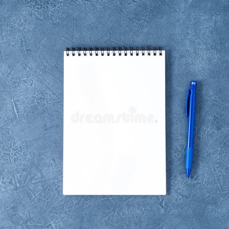 Il blocco note aperto con la pagina bianca pulita sulla tavola di pietra blu scuro invecchiata, vista superiore fotografia stock