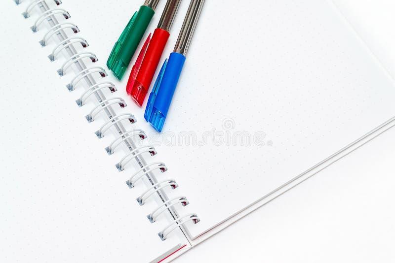 Il blocco note con fondo bianco e tre hanno colorato le penne immagini stock