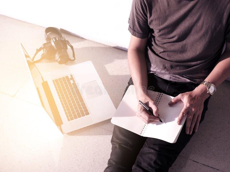 Il blog di stile di vita della gente di Digital elabora la penna sul taccuino e lo studio sul computer portatile, un uomo per ril fotografia stock