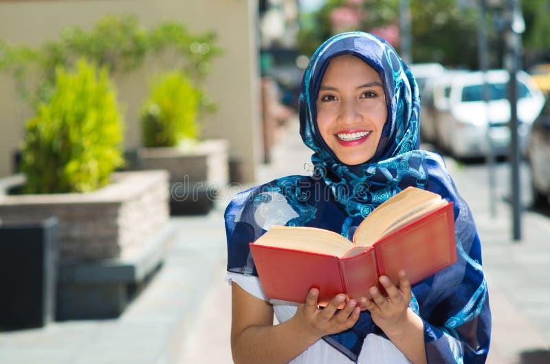 Il blu d'uso della bella giovane donna musulmana ha colorato il hijab, tenendo il libro a lamella spesso e leggendo in via, all'a fotografie stock libere da diritti