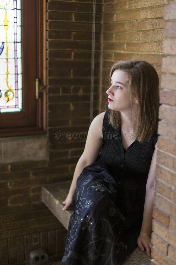 Il blu sbalorditivo ha osservato la ragazza nel profilo con l'espressione vaga che si siede sul banco di pietra fotografia stock libera da diritti
