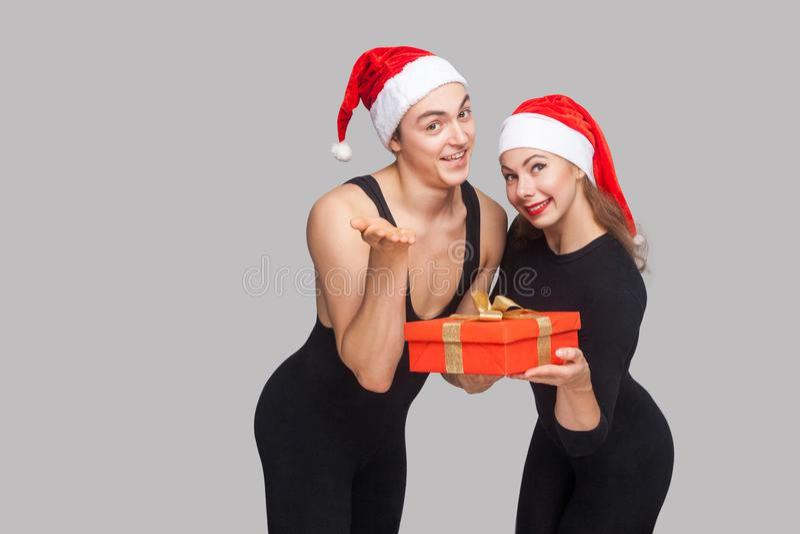 Il boîte-cadeau du ` s pour vous ! couples dans la position de chapeau de Noël et shar image stock