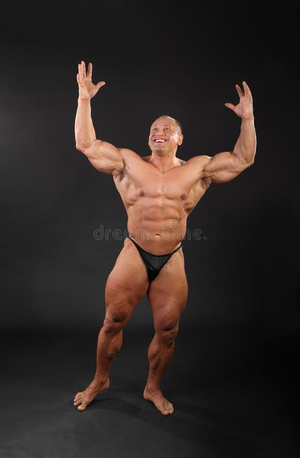 Il bodybuilder non condito solleva le mani in su fotografia stock libera da diritti