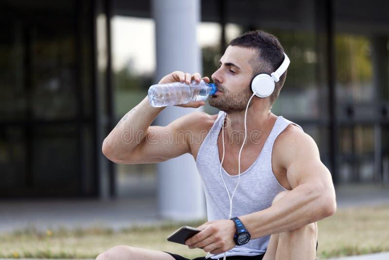 Il boit l'eau de la bouteille et des repos en parc après trai photos stock