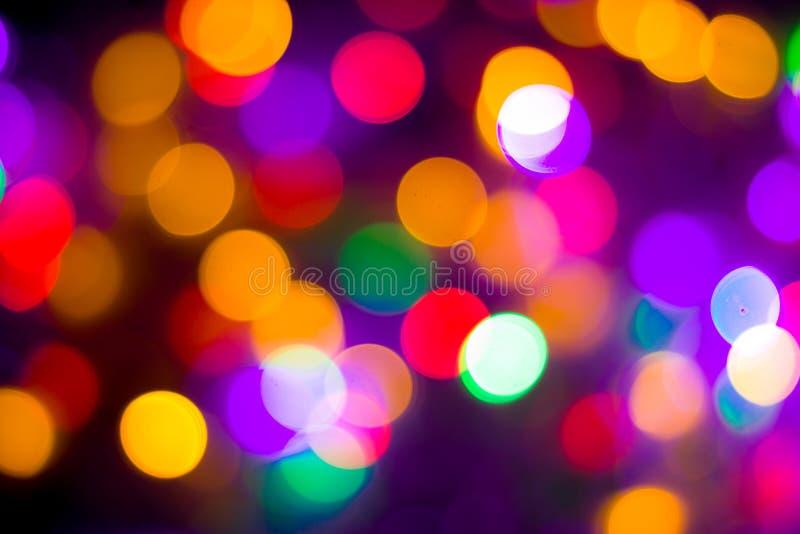 Il bokeh multicolore astratto Defocused accende il fondo Colori blu, porpora, verdi, arancio - concetto del nuovo anno e di natal immagine stock