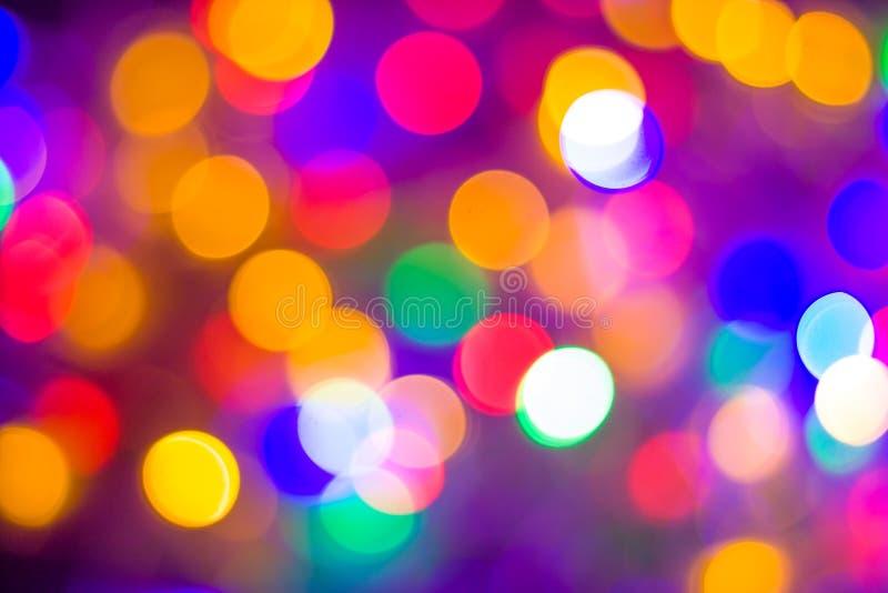 Il bokeh multicolore astratto Defocused accende il fondo Colori blu, porpora, verdi, arancio - concetto del nuovo anno e di natal fotografia stock