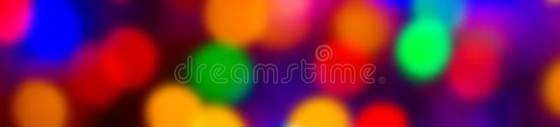 Il bokeh multicolore astratto Defocused accende l'ampio fondo dell'insegna Colori blu, porpora, verdi, arancio - natale e nuovo a immagine stock