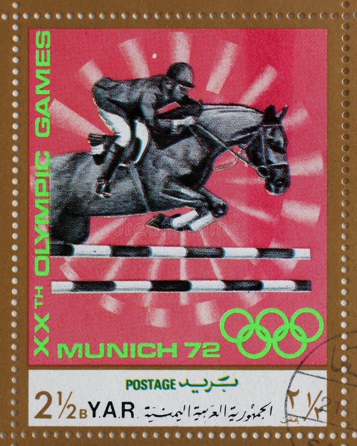 Il bollo stampato in Repubblica Araba Yemenita mostra la corsa di cavalli, Olympics a Monaco di Baviera immagini stock libere da diritti