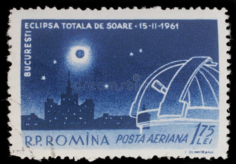Il bollo stampato in Romania mostra l'eclissi totale sopra l'edificio e l'osservatorio di Scanteia immagini stock libere da diritti