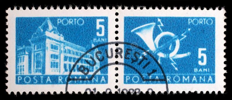 Il bollo stampato in Romania mostra la costruzione centrale dell'ufficio postale fotografie stock