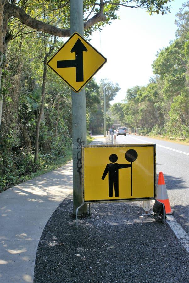 Il bordo del segno del segnale stradale della tenuta dell'uomo per traffico cambia immagine stock