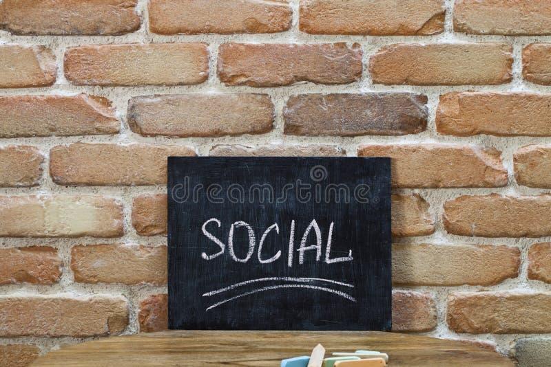 Il bordo di gesso con la parola SOCIALE annega a mano e segna sulla tavola di legno sul fondo del muro di mattoni fotografia stock