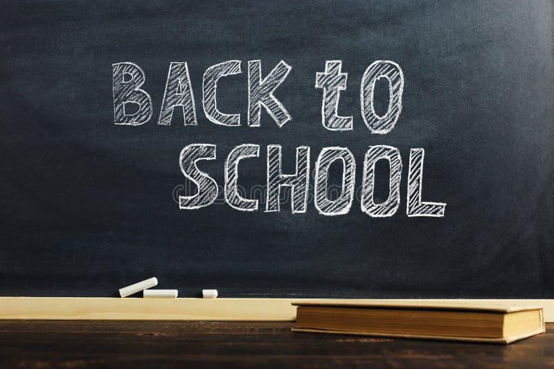 Il bordo di gesso nero sopra la tavola di legno con il libro, soppressione per testo o fondo per il tema della scuola immagine stock libera da diritti