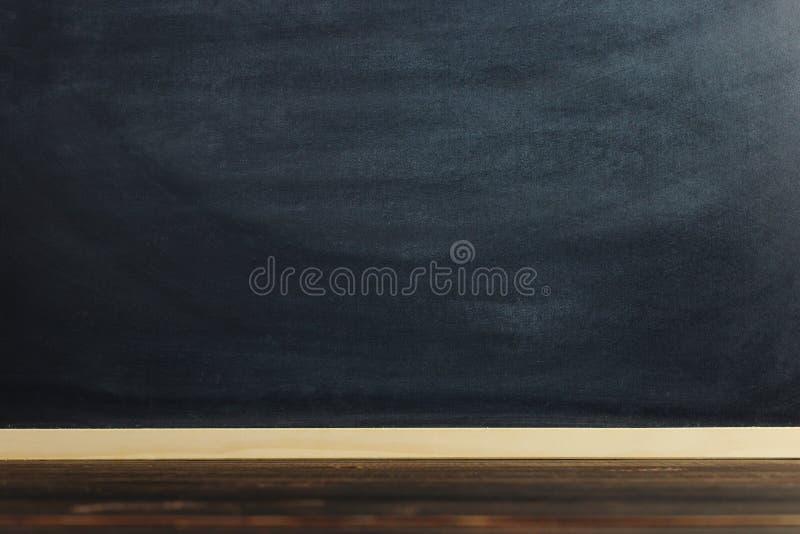 Il bordo di gesso nero sopra la tavola di legno, soppressione per testo o fondo per un tema della scuola fotografia stock libera da diritti