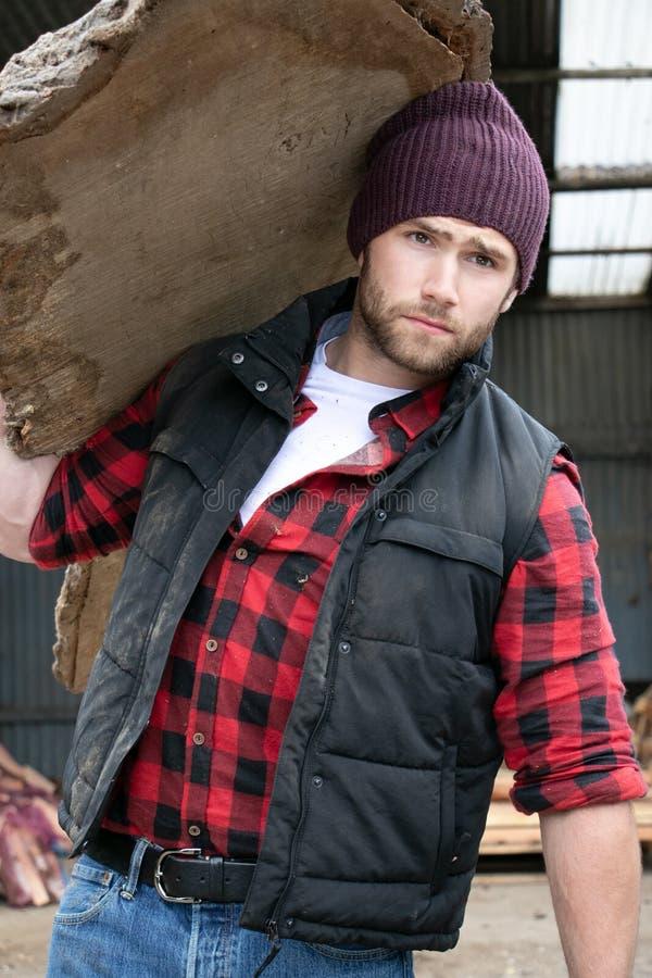 Il boscaiolo maschio bello porta il collegamento di legno la sua spalla fotografie stock libere da diritti