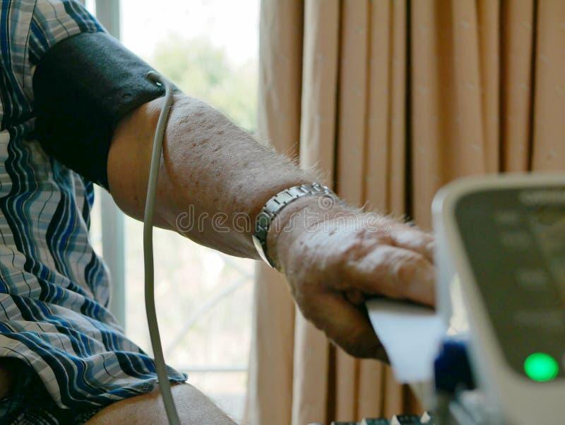 Il braccio di un uomo anziano con un polsino di pressione sul controllo della sua pressione sanguigna a casa solo immagini stock libere da diritti