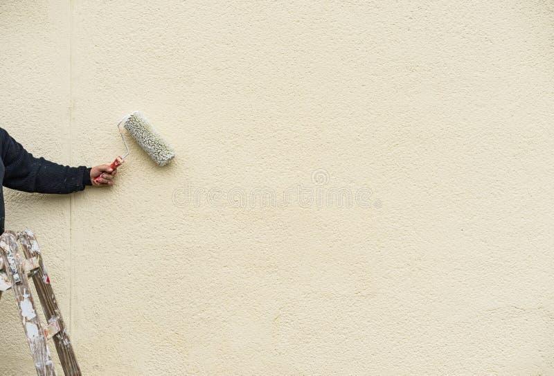 Il braccio maschio con il rullo del pittore sulla scala dipinge la parete bianca fotografia stock libera da diritti