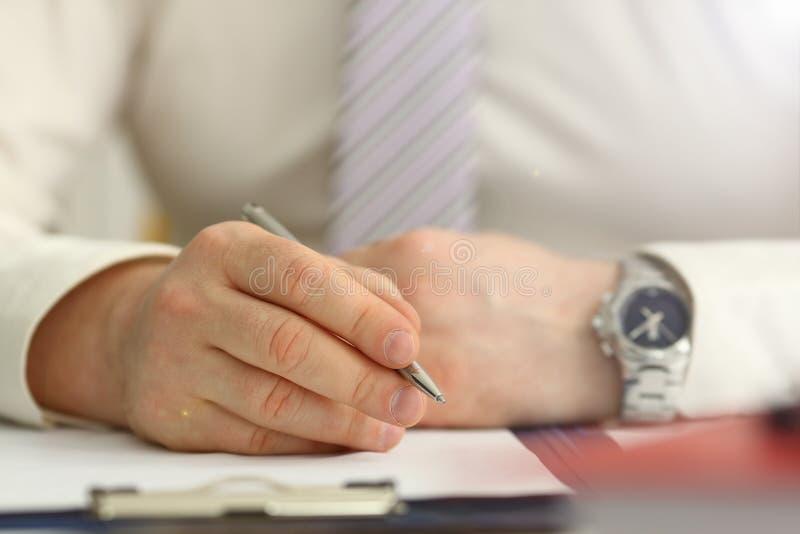 Il braccio maschio in vestito ed il legame tengono la penna d'argento immagini stock libere da diritti