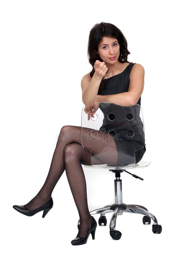 Il brunette splendido si è seduto sulla presidenza immagini stock