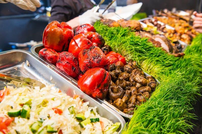 Il buffet culinario di cucina all'aperto con sano porta via il pasto - le verdure arrostite, le insalate, carne sul mercato culin fotografia stock libera da diritti