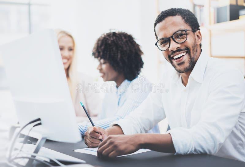 Il buio ha pelato i vetri d'uso dell'imprenditore, lavoranti nell'ufficio moderno Uomo afroamericano in camicia bianca che sorrid immagini stock