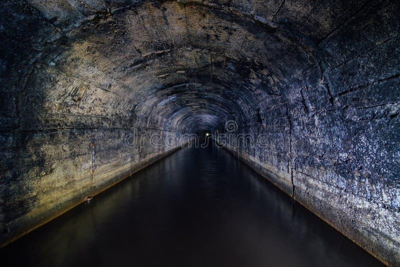 Il buio ha sommerso il tunnel arcato concreto della miniera di drenaggio immagini stock libere da diritti