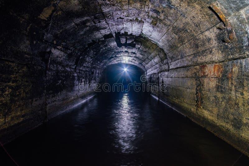 Il buio ha sommerso il tunnel arcato concreto della miniera di drenaggio fotografie stock