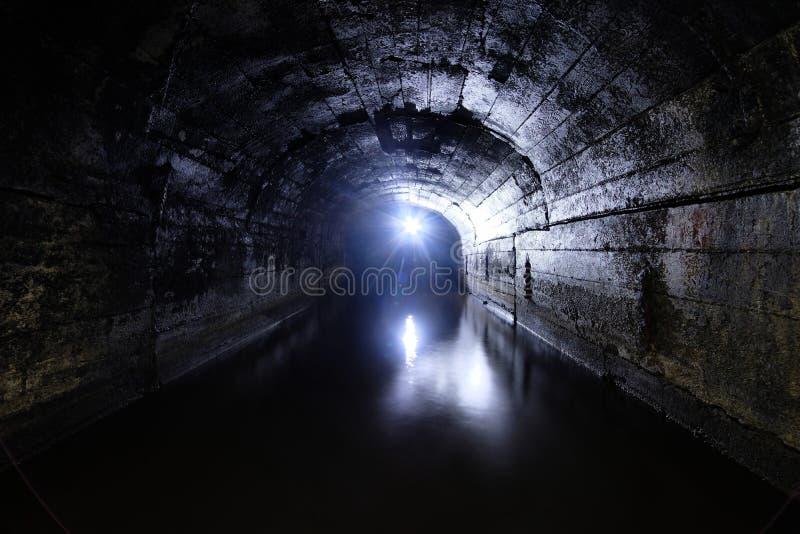 Il buio ha sommerso il tunnel arcato concreto della miniera di drenaggio fotografia stock libera da diritti
