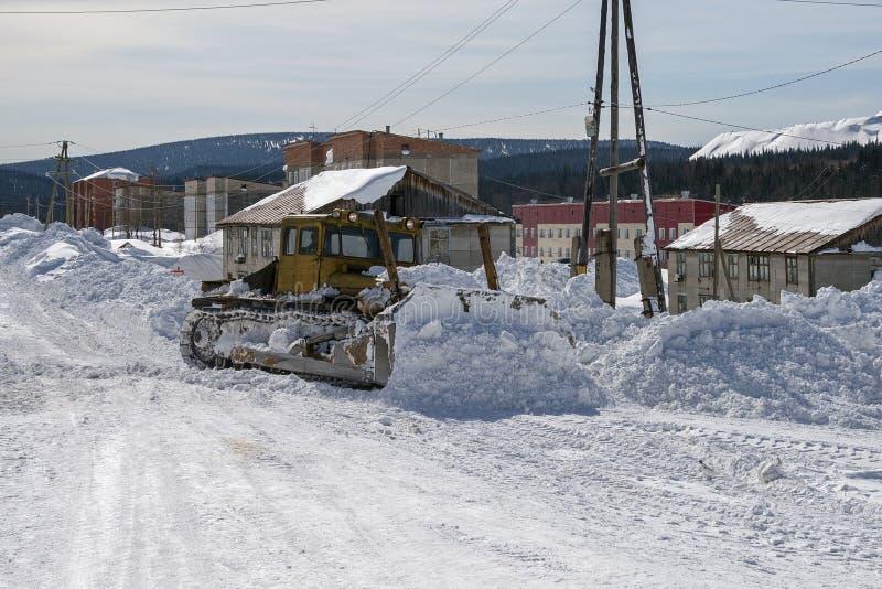 Il bulldozer libera la strada dalla neve sulla via immagine stock