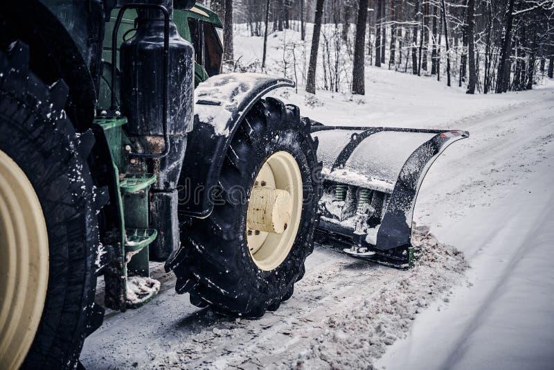Il bulldozer pulisce la strada innevata attraverso la foresta immagine stock