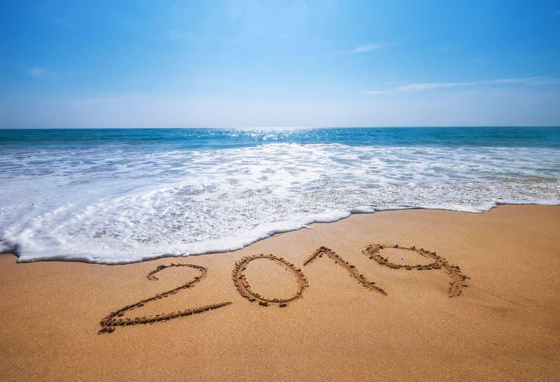 Il buon anno 2019 è spiaggia tropicale sabbiosa venente dell'oceano di concetto immagine stock libera da diritti