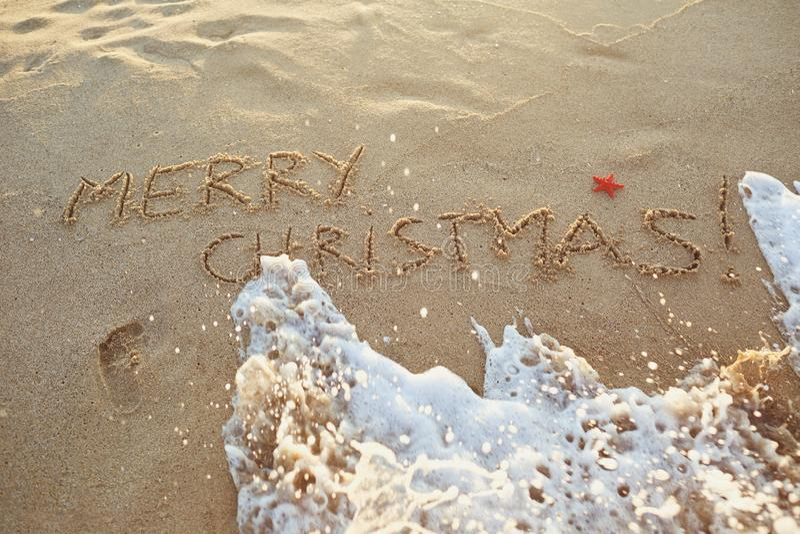 Il Buon Natale dell'iscrizione sulla sabbia sulla spiaggia fotografia stock libera da diritti