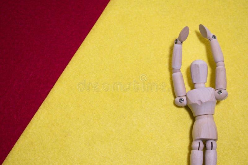Il burattino di legno sul feltro rosso e giallo dell'acrilico di colore sostiene le armi fotografia stock libera da diritti