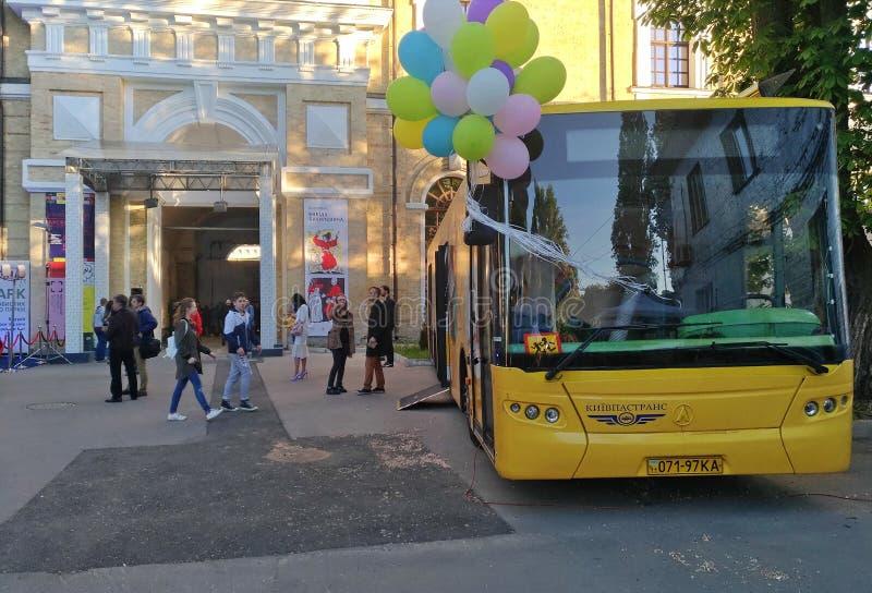 Il bus giallo con i palloni variopinti sta alla mostra del libro nel museo dell'arsenale a Kiev fotografia stock libera da diritti