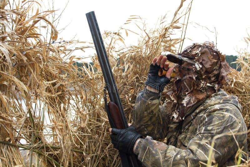 Il cacciatore attira le anatre con la chiamata dell'anatra immagine stock libera da diritti