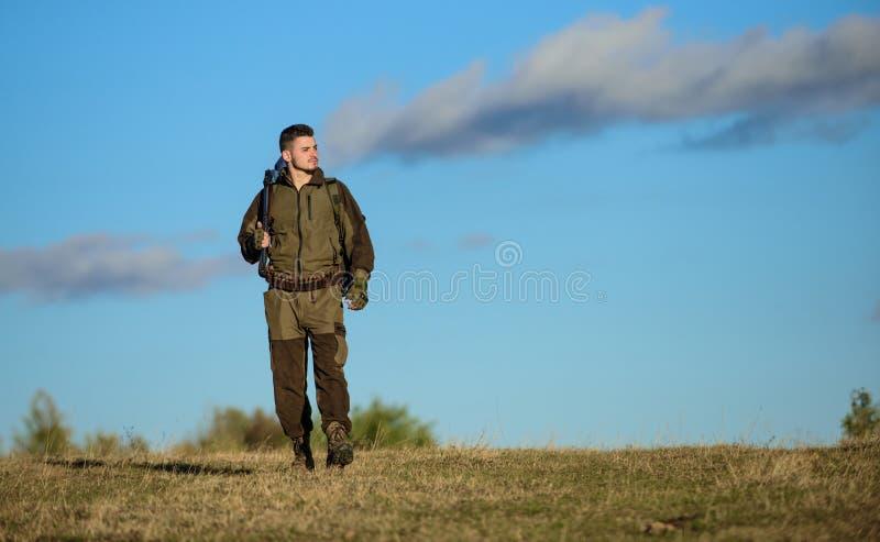 Il cacciatore dell'uomo porta il fondo del cielo blu del fucile L'esperienza e la pratica presta la caccia di successo Hobby di c fotografie stock
